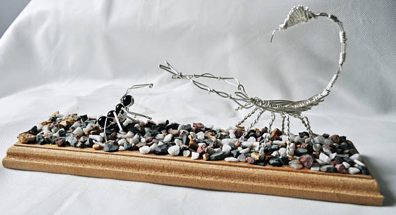 Ant made of silver plated wire fighting a Scorpion sculpture mounted on wood