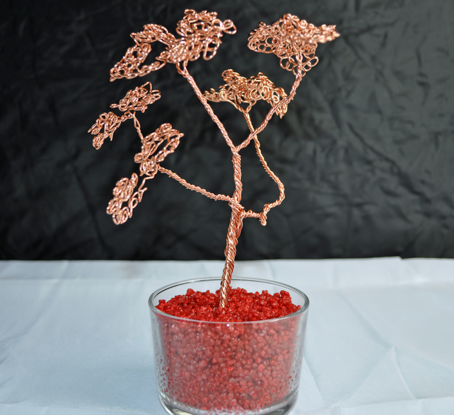 A Copper wire bonsai tree  tree in a glass dish with beautiful red stones
