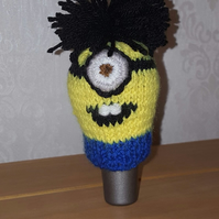 a hand knitted gear knob beanie hat in yellow minion or purple minion designs