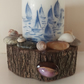 Hand decorated small white pillar candle with blue boats on a wooden base