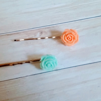 Orange and green pastel coloured  floral bobby pins on a cold coloured pin