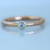 Red gold, or rose gold halo band with white gold setting and 3mm diamond.