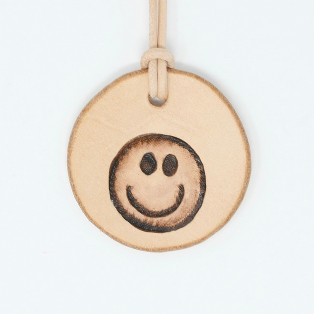 Leather pendant with smiley face motif