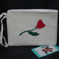 Small white wristlet clutch bag with appliqued rose in one of three colours