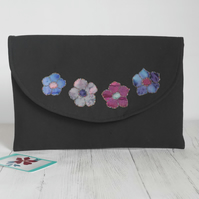 Black clutch bag made from upcycled fabric, with appliqued flowers