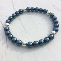 Stretch bracelet with petrol blue beads and silver plated beads