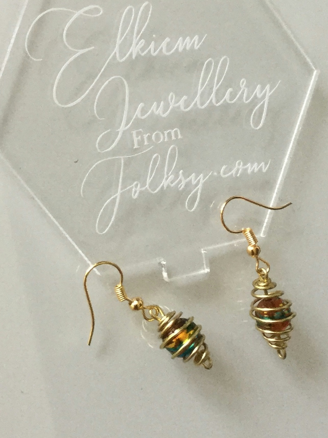 Earrings from a crackle glass bead inside a golden cage