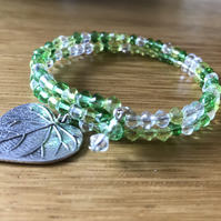 Green and clear beaded memory wire bracelet with silver metal leaf