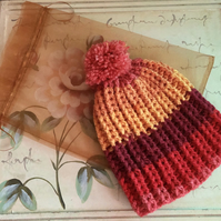 "Womens warm bobble hat in ""sunset"" shade."