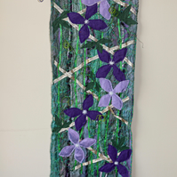 Machine embroidered and appliqué wallhanging of clematis climbing up trellis
