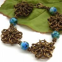 Celtic weave chain maille flower bracelet with blue glass beads