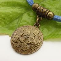 Flower motif medallion charm necklace on blue cord