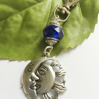 Sun and moon motif bag charm with blue glass bead