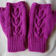 Hand knitted raspberry pink Celtic heart cable pattern fingerless mitts