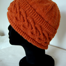 Hand knitted burnt orange ladies' Celtic heart pattern cable hat