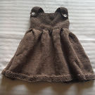 A hand knitted dress aged 6-12 months.