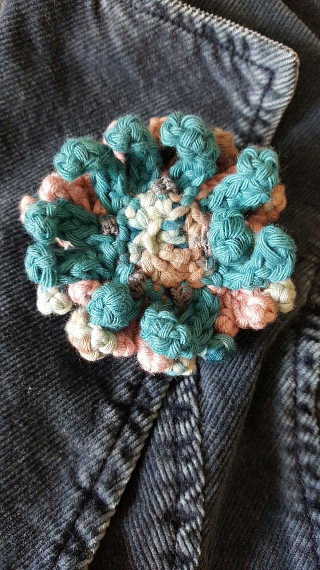 Crocheted flower brooch. Handmade floral decoration.