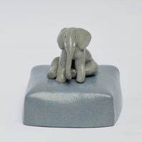 Baby elephant resting on a blue base - ceramic ornament