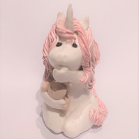 Baby Unicorn sucking thumb and hugging teddy bear  in porcelain