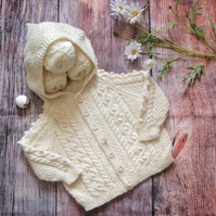 Baby's hand knitted off-white cream cable aran hoody cardigan jacket with hood