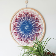 Galaxy crochet wall hanging, blue and purple, 60cm in diameter.