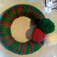 Wreath in red and green wool with pompoms.