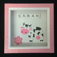 A personalised cow picture, with a wooden cow & white wooden scrabble letters.