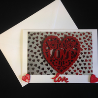 A photo of a red heart saying love, with hand painted wooden details.