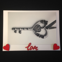 A black & white photo of a key saying love, with hand painted wooden details.