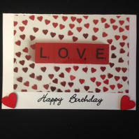 A photo of red scrabble letters saying love with hand painted wooden hearts.