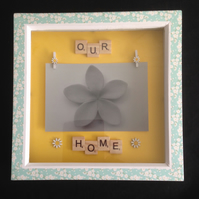 "Scrabble photo frame saying ""Our home"" with wooden details."