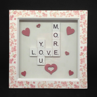Love you more, scrabble picture with wooden hearts.