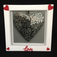 A photo of a silver heart, in a white frame with hand painted wooden details.