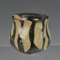 A stoneware guinomi with black slip decoration