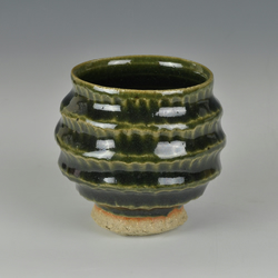 A carved, stoneware sake cup with Japanese style Oribe glaze