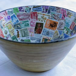 Deep wooden bowl decoupaged with colourful world stamps