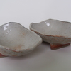 A pair of thrown and altered bowls glazed in shino.