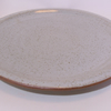 Hand thrown dinner plate with raised side. Glazed in speckled white. 26 cm.