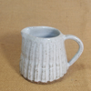 Stoneware fluted jug with speckled white glaze.