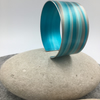 Turquoise and grey anodised aluminium striped cuff