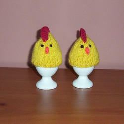 A pair of hand knitted chicken egg cosies