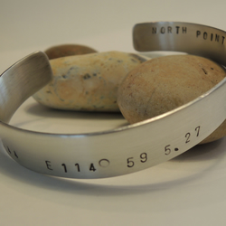 Man's silver latitude and longitude bracelet with hidden message