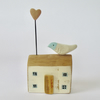 Little wooden house with a clay bird and heart