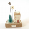 Little wooden house with Christmas tree, star and button