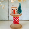 Little wooden Christmas house on a vintage bobbin