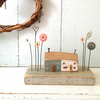 Little wooden painted houses with button flower garden