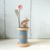Little oak house with clay flower and bird on wooden bobbin