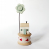 Tiny oak house with clay flower on vintage wooden bobbin