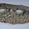 Twin glass tealight holder & tealight on pebble beach with a driftwood backdrop.