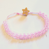 Pink beaded bracelet with wooden star button.